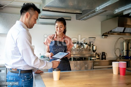 178974134 istock photo Customer paying using contactless payment option in a cafe 1132067045