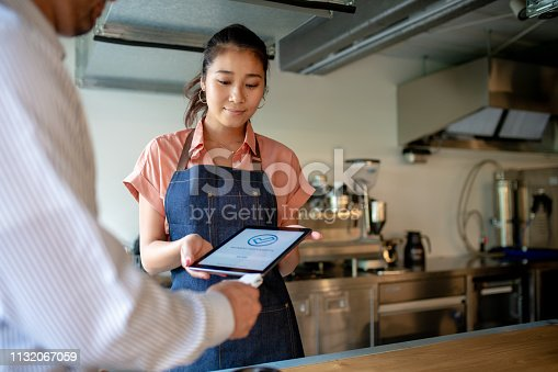 178974134 istock photo Customer paying using contactless payment option in a cafe 1132067059