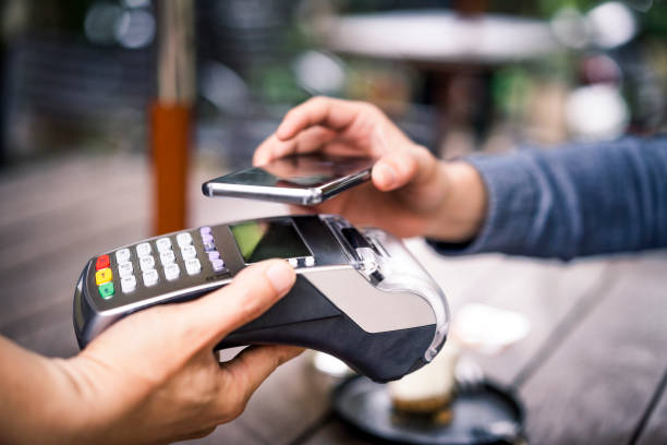 Customer paying using mobile payment to cafe owner stock photo