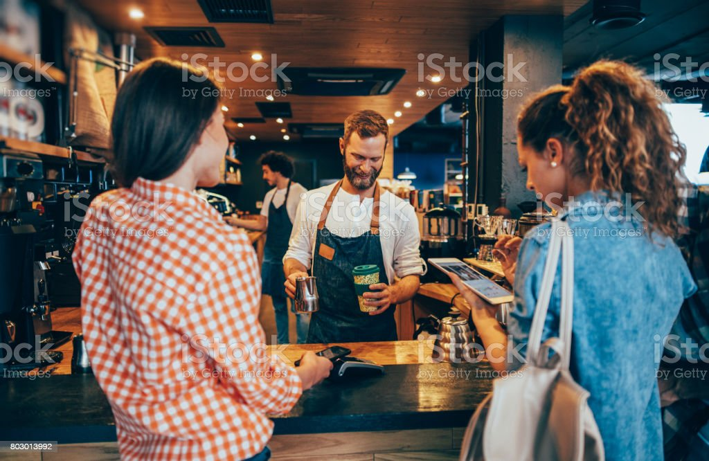 Customer paying while getting her order stock photo