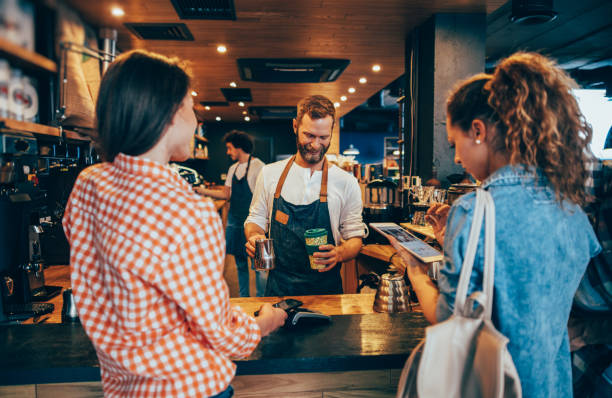 customer paying while getting her order - barista stock photos and pictures