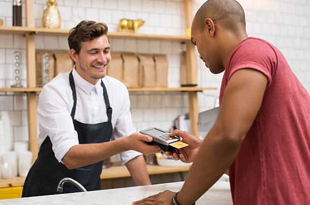 Customer paying with credit card Waiter holding credit card swipe machine while customer typing code. African young man making payment in cafeteria with credit card. Customer paying for coffee and brunch by credit card reader. smart card stock pictures, royalty-free photos & images
