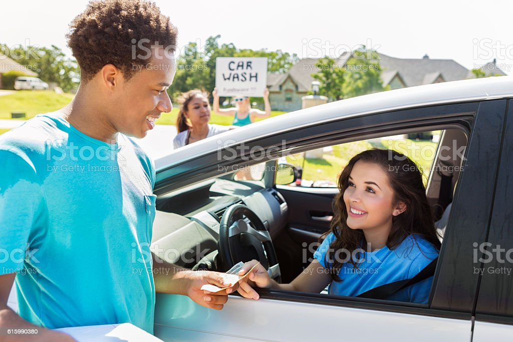 Customer pays volunteer after car is washed at a fundraiser stock photo