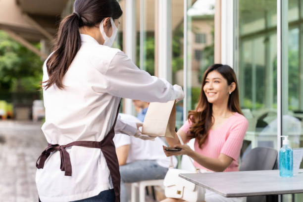 Customer pick up takeout food order from waitress Back view of asian waitress with face mask give order of take out food bag to attractive woman female customer. Take away or take-out food service concept in new normal after coronavirus pandemic. curbsidepickup stock pictures, royalty-free photos & images