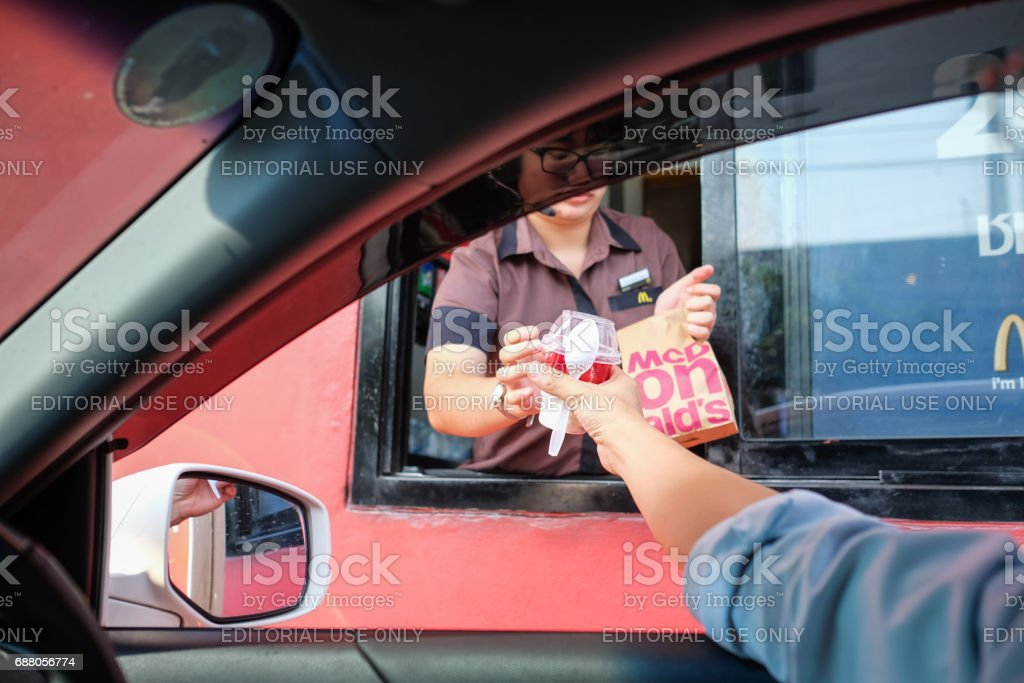 Customer receiving hamburger and ice cream after order and buy it from McDonald's drive thru service stock photo