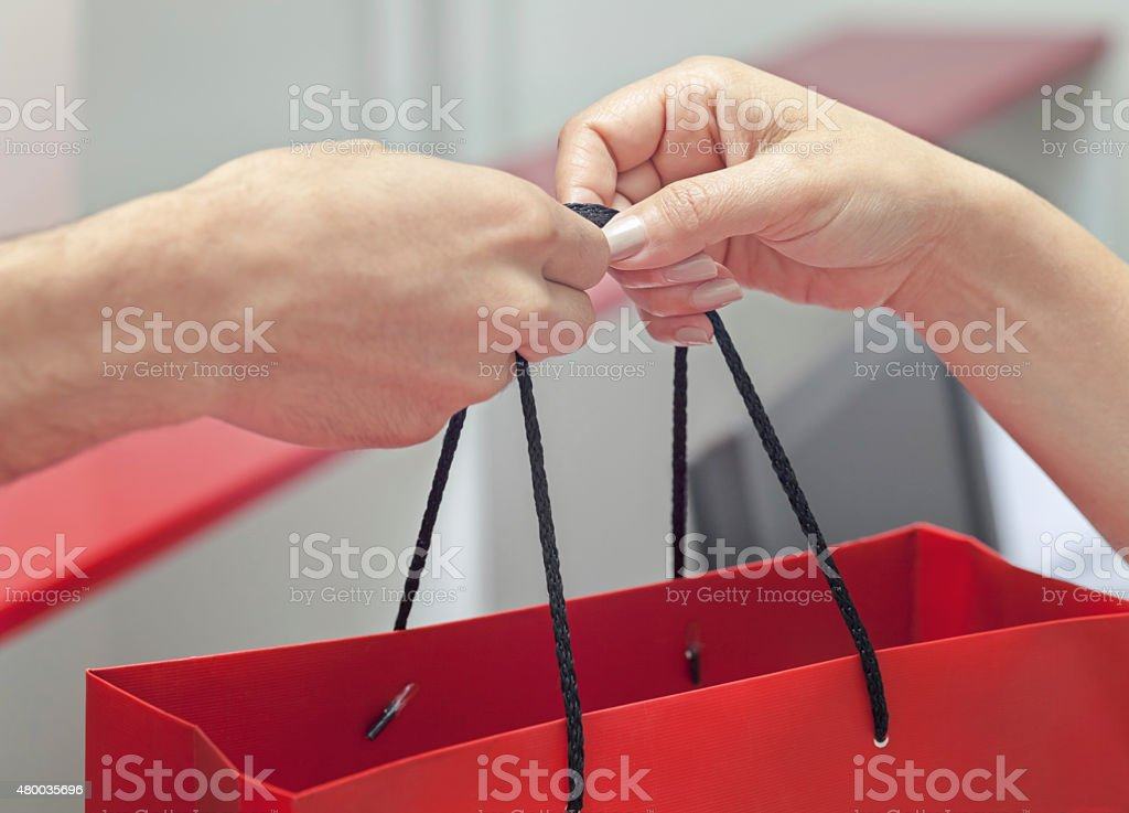 Customer receiving shopping bag from cashier stock photo