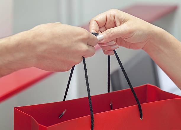 Kunden erhalten Einkaufstasche an Kasse – Foto
