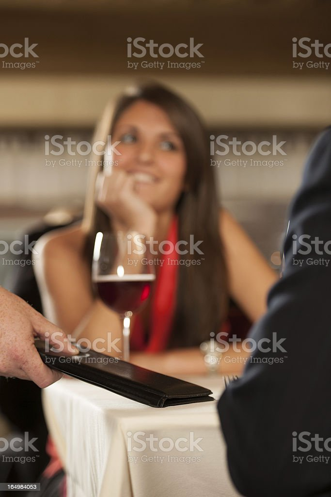 Man and woman, on a date at resturant, recieve check from waiter.