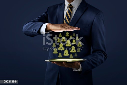 istock Customer relationship management (CRM) concept for business and finance. Businessman is showing customer icons that projected from tablet on dark tone background. 1090313984