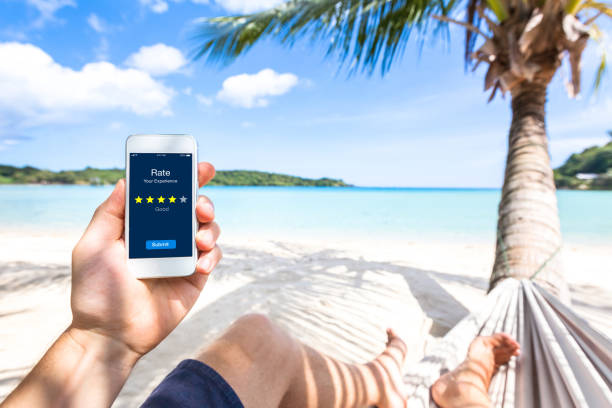 Customer review on smartphone screen, rate experience, feedback, stars, beach stock photo