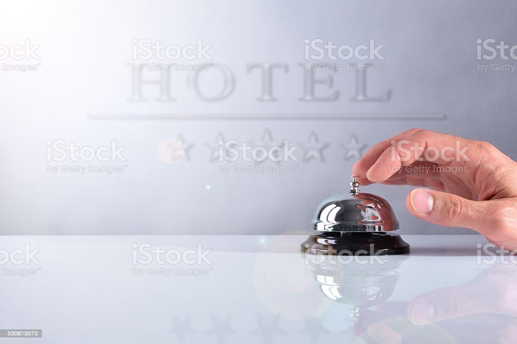 Customer ringing the bell hotel service with placard front view stock photo