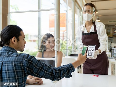 Asian customer scan QR code online menu from waitress with face mask and face shield. Customer sat on social distancing table for new normal lifestyle in restaurant after coronavirus covid-19 pandemic.