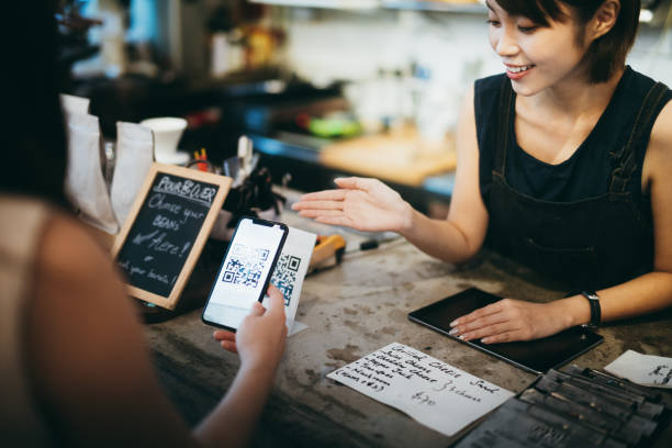 Customer scanning QR code, making a quick and easy contactless payment with her smartphone in a cafe in front of a smiling barista