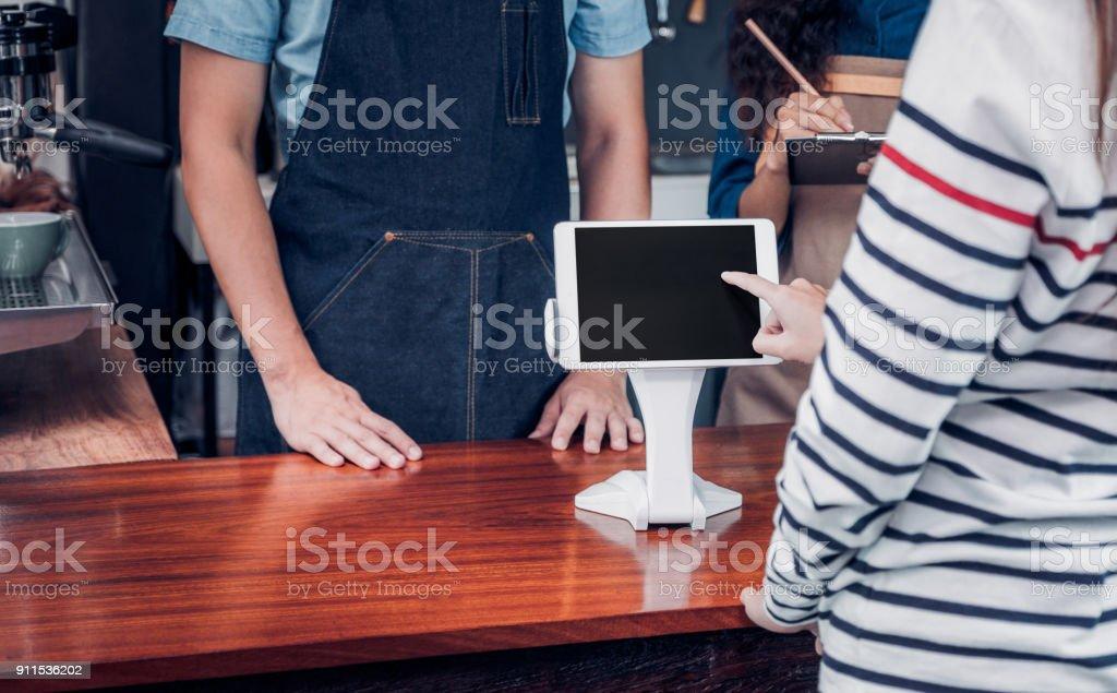 klant zelf serviceorder drank menu met Tablet PC-scherm bij café teller bar, coffeeshop verkoper betaling accepteren door mobile.digital levensstijl concept. Lege ruimte voor de weergave van design.clipping pad. foto