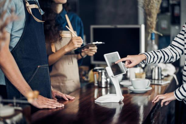 客戶自助服務訂單飲料功能表在咖啡館櫃檯酒吧, 賣家咖啡店接受移動支付. 數位生活方式概念。用於顯示設計的空白空間。 - 吧 公共飲食地方 個照片及圖片檔