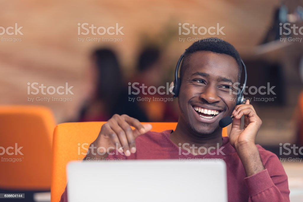 Customer Service agent in an startup office with laptop stock photo