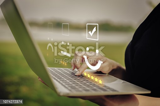 Businesswoman pressing face emoticon on the keyboard laptop / Customer service evaluation concept.