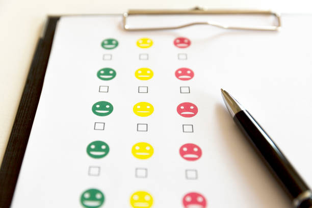 Customer service evaluation survey with smiley faces and pen. stock photo