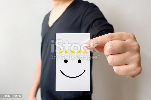 693589426 istock photo Customer service experience and business satisfaction survey. Man holding card with smiley face with five star 1166193576