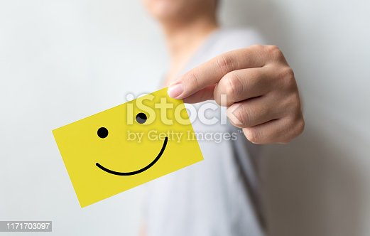 693589426 istock photo Customer service experience and business satisfaction survey. Man holding yellow card with smiley face 1171703097
