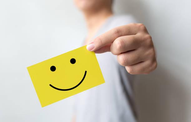 Kundendiensterfahrung und Umfrage zur Geschäftszufriedenheit. Mann hält gelbe Karte mit Smiley-Gesicht – Foto