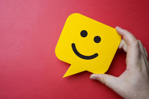 kundendiensterfahrung und umfrage zur geschäftszufriedenheit. mann hält gelbe sprechblase mit smiley-gesicht auf rotem hintergrund. - glücklichsein stock-fotos und bilder