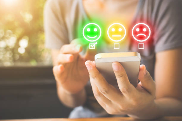 Customer Service Experience and Business Satisfaction Survey. Woman choose face smile on smart phone Customer Service Experience and Business Satisfaction Survey. Woman choose face smile on smart phone wisdom stock pictures, royalty-free photos & images