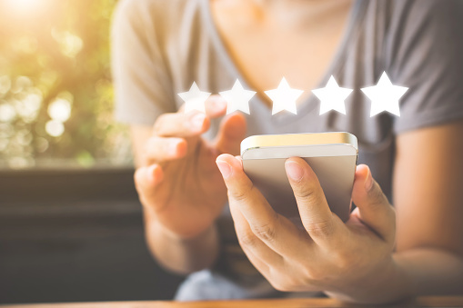 917079212 istock photo Customer service experience and business satisfaction survey. Woman hand using smart phone with icon five star symbol to increase rating of company concept 1144247593
