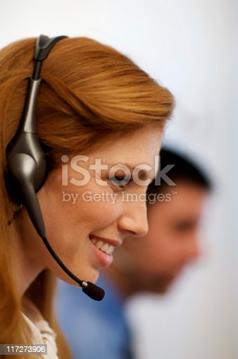 Attractive young woman wearing a headset with collegue in the background. Vertical shot.