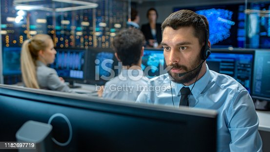 istock Customer Service Representative Answer Client's Questions in a Headset. He Works for a Big Technological Company. Office Has Multi-Ethnic Team of Specialists, Displays Show Useful Information. 1182697719