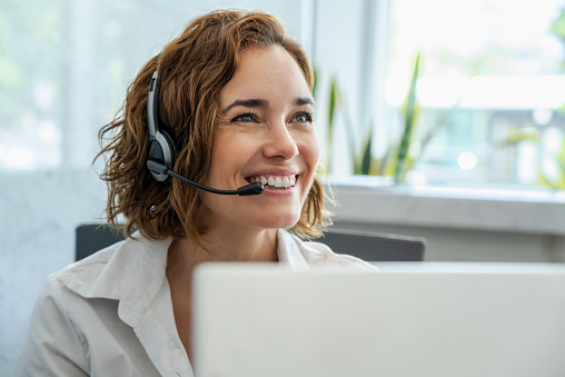 Close-up of smiling mature female customer service representative wearing headset in office