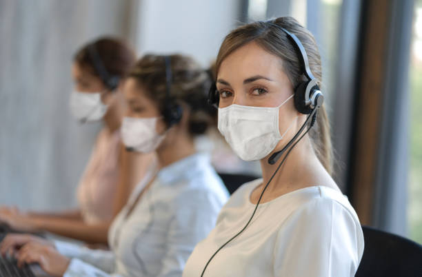 Customer service representative working at a call center wearing facemask during the COVID-19 pandemic stock photo