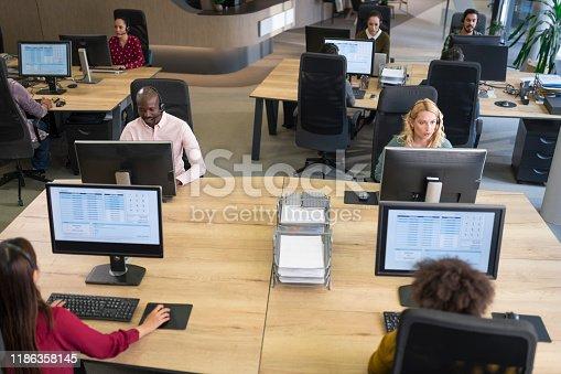 Customer service representatives using desktop computers in call centre.