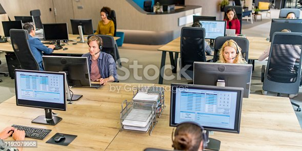 Customer service representatives working at their desktop computers in call centre.