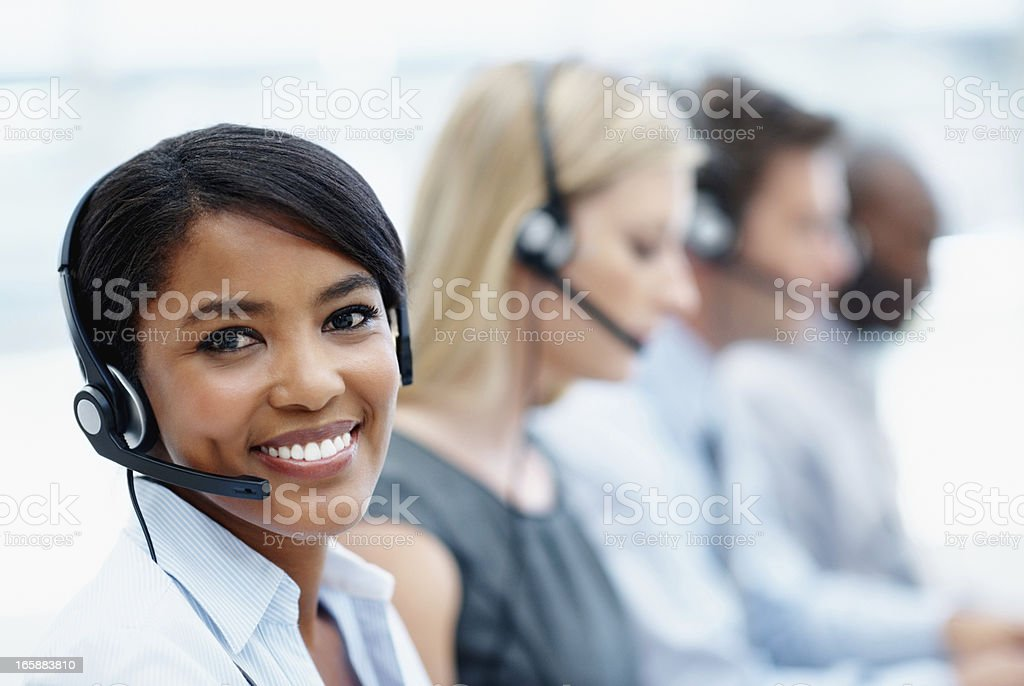 Customer service team wearing headsets with businesswoman in front royalty-free stock photo