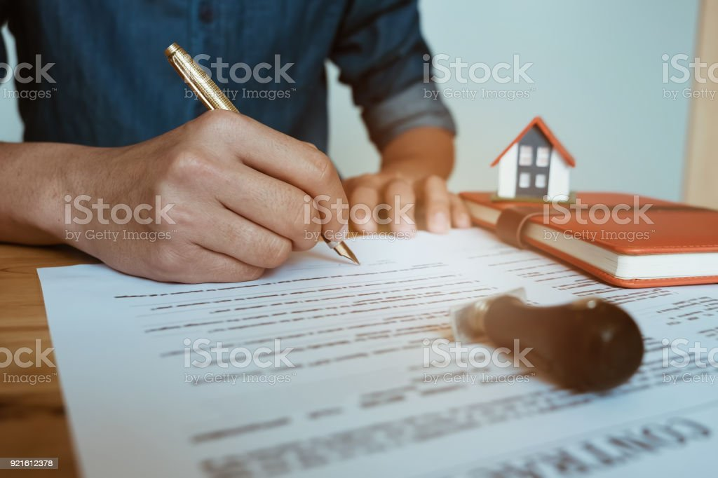 customer sign contract and pressing rubber stamp on house contract document. Agreement concept. stock photo