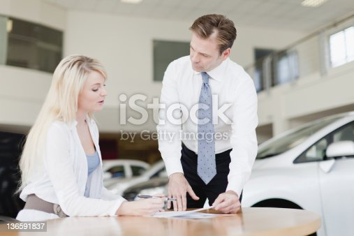136591850 istock photo Customer signing at car dealership 136591837