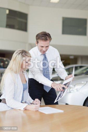 136591825istockphoto Customer signing at car dealership 136591838