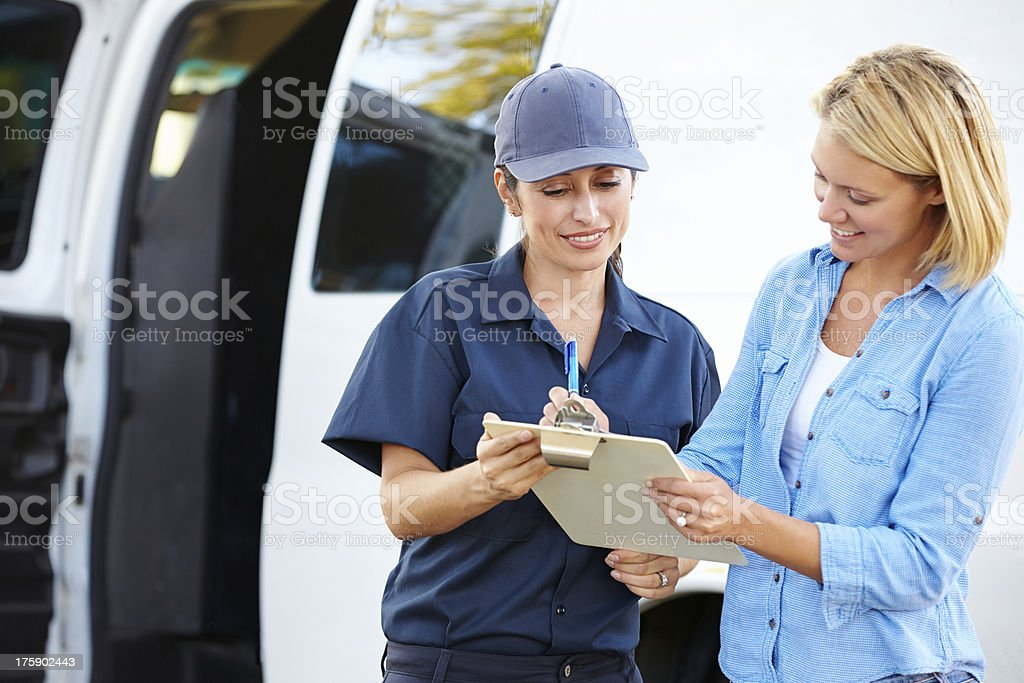 Customer Signing For Delivery From Female Courier stock photo