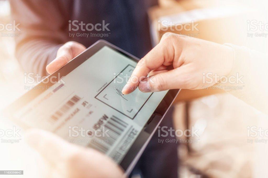 Kunden unterzeichnen Empfang der Hauszustellung auf einem Tablet - Lizenzfrei Arbeiten Stock-Foto