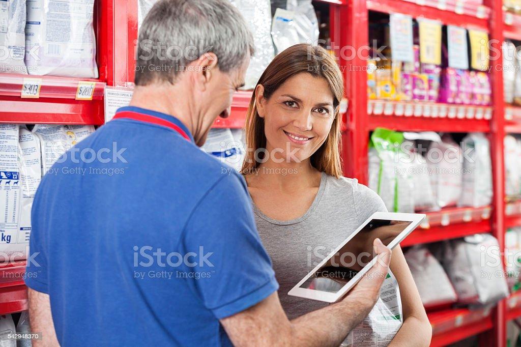 Customer Standing By Salesman Using Digital Tablet In Pet Store stock photo