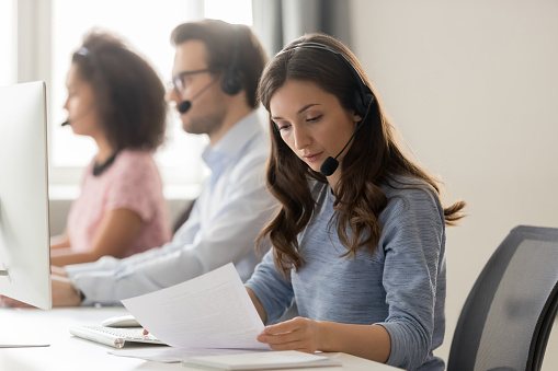 istock Customer support phone operator sitting at workplace holds read document 1147384838