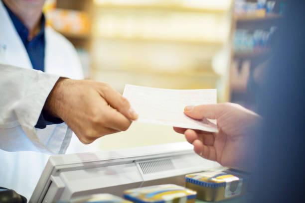 kunden nehmen rechnung vom männlichen apotheker im store - alvarez stock-fotos und bilder