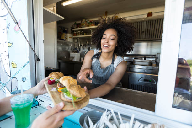 Customer taking burgers from food van Male customer boying sandwiches and burgers from food van. food truck stock pictures, royalty-free photos & images