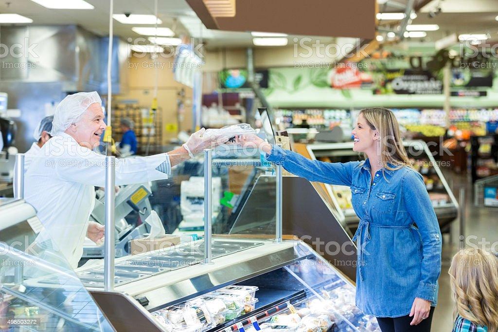 Kunde nimmt package von senior deli manager in einem Supermarkt – Foto