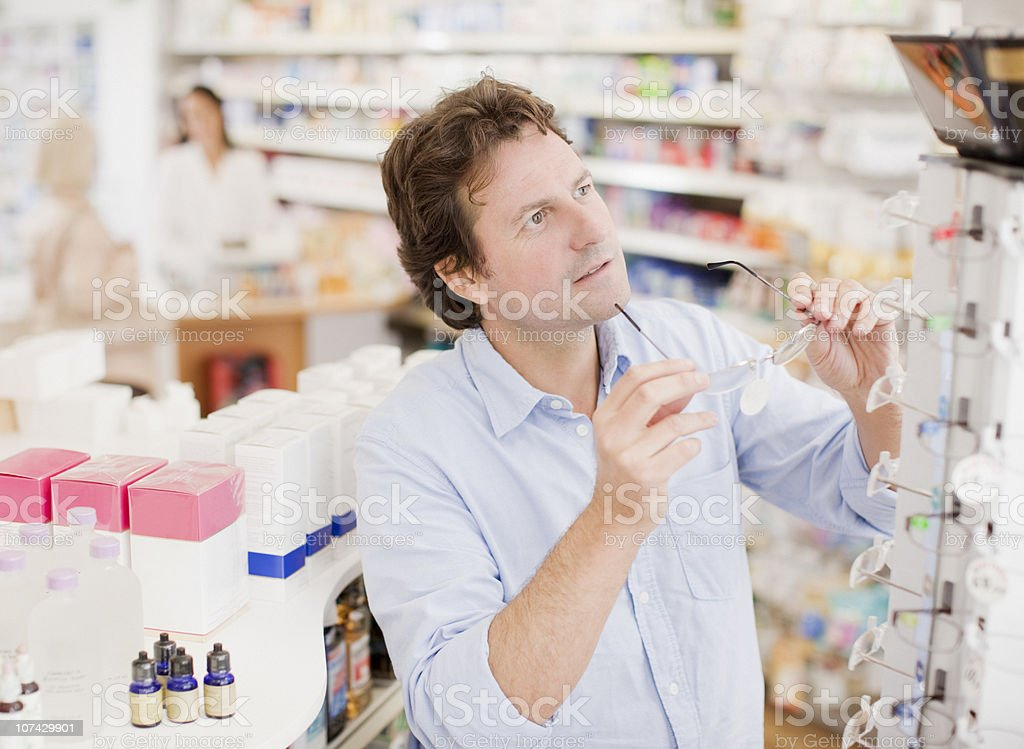 Customer trying in prescription eyeglasses in drug store royalty-free stock photo