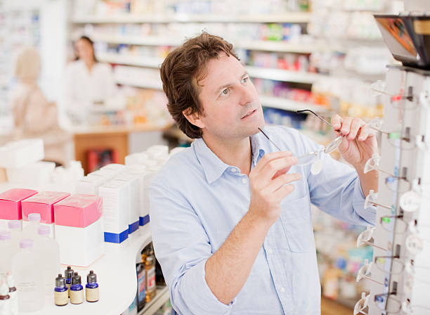 Customer trying in prescription eyeglasses in drug store stock photo
