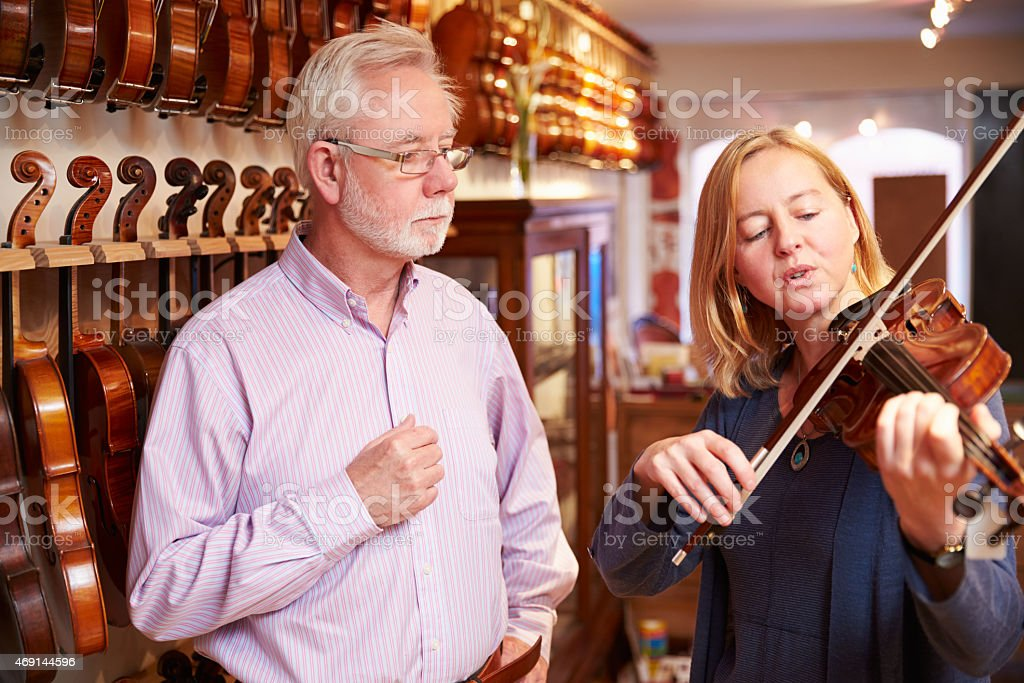 Customer Trying Out Violin In Music Store stock photo