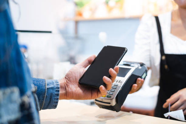 Customer using mobile phone scanning for payment to owner at cafe restaurant, cashless technology and credit card payment concept stock photo