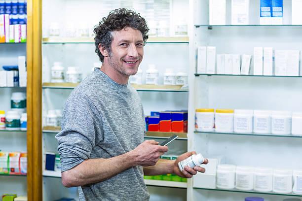customer using phone with drug in hand - lieblingsrezepte stock-fotos und bilder